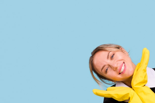 Glückliche junge frau mit dem gelben handschuh, der über blauem hintergrund aufwirft