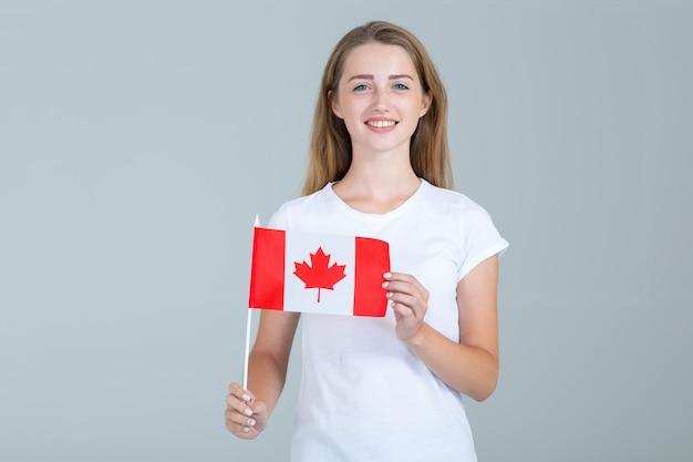 Glückliche junge frau mit der flagge von kanada auf grau
