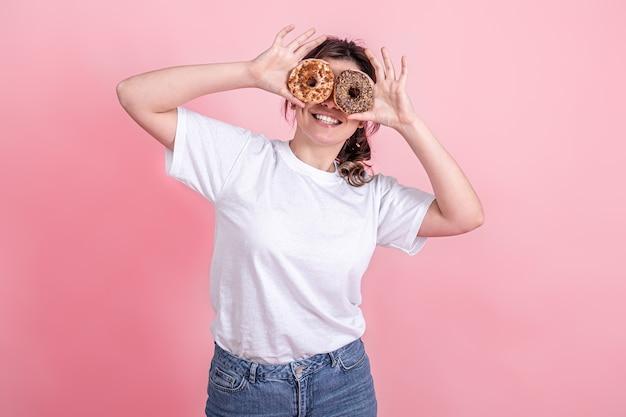 Glückliche junge frau mit donuts in ihren händen lächelt, hält rosa donuts in der nähe ihrer augen ihre hände, rosa hintergrund.