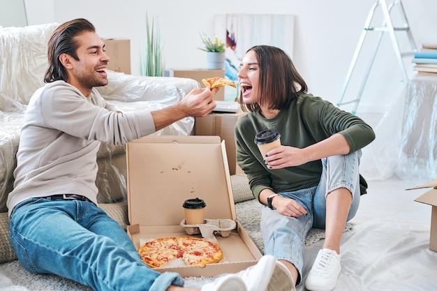 Glückliche junge frau mit einem glas kaffee zum mitnehmen, der den mund öffnet, während ihr ehemann ihr stück pizza während des mittagessens auf dem boden gibt