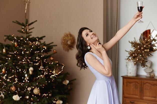 Glückliche junge frau mit einem glas wein in ihrer hand, die im innenraum mit weihnachtsbaum aufwirft