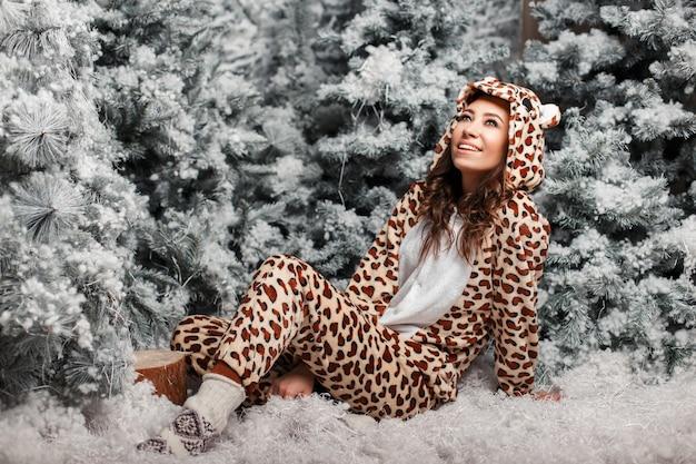 Glückliche junge frau mit einem lächeln in einem lustigen bärenpyjama, der nahe einem weihnachtsbaum mit schnee ruht
