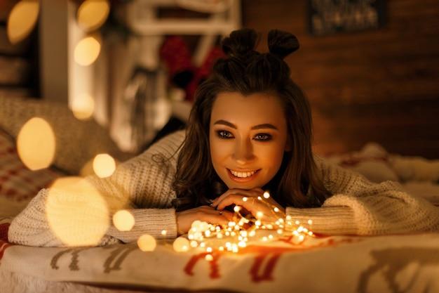 Glückliche junge frau mit einem lächeln in einem weinlese-strickpullover mit festlichen lichtern, die auf dem bett ruhen