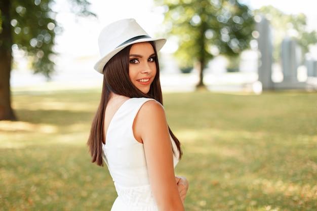 Glückliche junge frau mit einem lächeln in einem weißen kleid mit einem hut an einem sommertag an der frischen luft