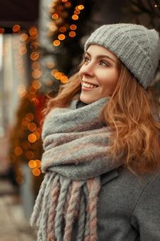 Glückliche junge frau mit einem magischen lächeln in der mode stilvolle strickwaren mit einer gestrickten grauen mütze und einem schal nahe den lichtern an feiertagen Premium Fotos