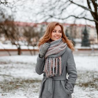 Glückliche junge frau mit einem niedlichen lächeln in den warmen handschuhen in einem modischen wintermantel mit einem gestrickten weinlese-schal, der in einem verschneiten park aufwirft