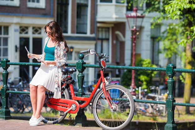 Glückliche junge frau mit einem stadtplan auf fahrrad in der europäischen stadt