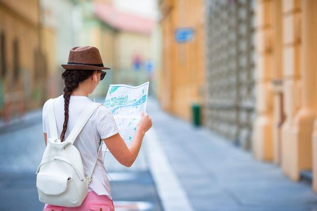 Glückliche junge frau mit einem stadtplan in der stadt. touristische frau der reise mit karte in prag draußen während der feiertage in europa.