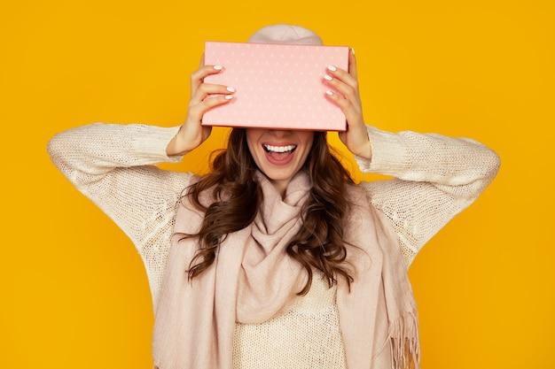 Glückliche junge frau mit einer geschenkbox in ihren händen, bedeckt die hälfte ihres gesichts mit einem neujahrsgeschenk. das mädchen zeigt der kamera ein geschenk. das konzept der geschenke und überraschungen für das neue jahr und weihnachten.