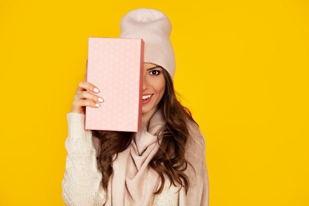 Glückliche junge frau mit einer geschenkbox in ihren händen, bedeckt die hälfte ihres gesichts mit einem neujahrsgeschenk.