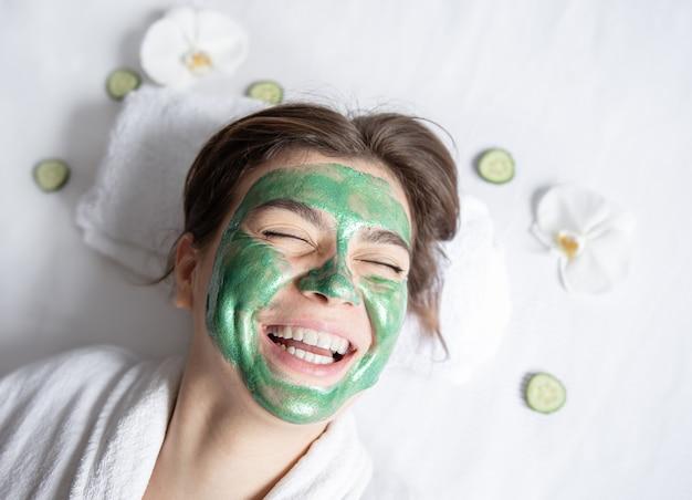 Glückliche junge frau mit einer grünen kosmetischen maske auf ihrer draufsicht des gesichts