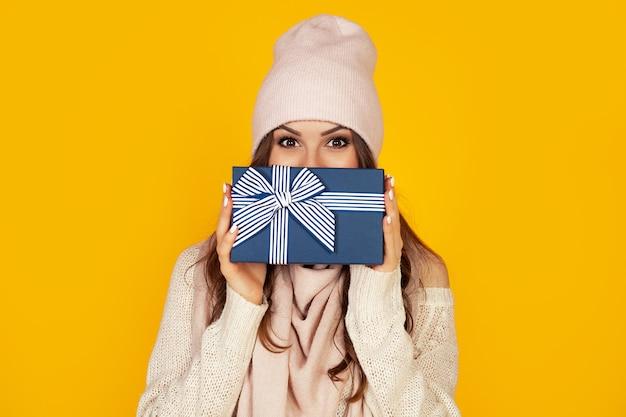 Glückliche junge frau mit einer weihnachtsgeschenkbox in ihren händen bedeckt die hälfte ihres gesichts