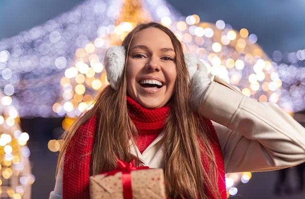 Glückliche junge frau mit geschenk lächelnd und warme ohrenschützer einstellen, während weihnachten in der nacht auf straße feiern