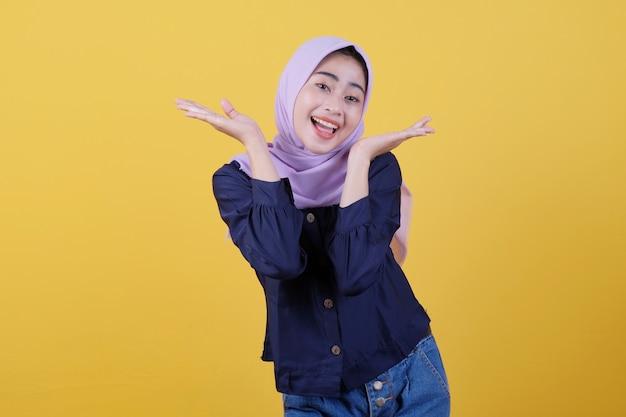 Glückliche junge frau mit glücklichem gesichtsausdruck zeigt etwas in ihrer hand mit hijab und freizeitkleidung in gelb