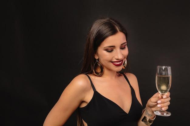 Glückliche junge frau mit goldenem schmuck im schwarzen kleid, das champagner trinkt
