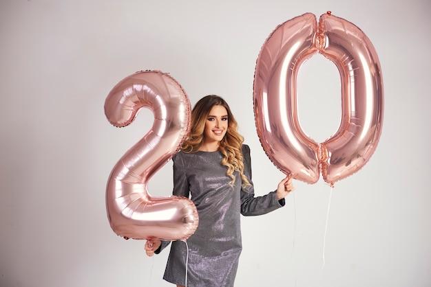 Glückliche junge frau mit goldenen luftballons, die ihren geburtstag feiern