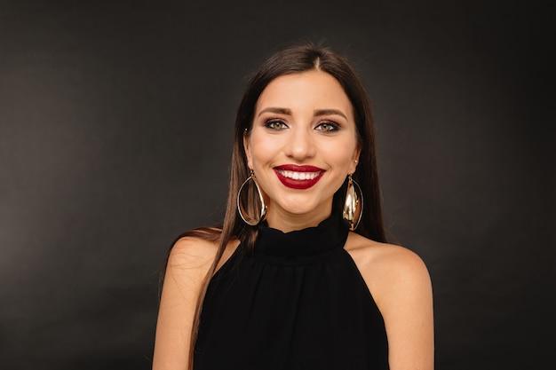 Glückliche junge frau mit hellem make-up und goldenem juwelen im schwarzen kleid, das aufwirft