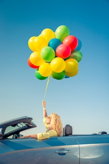 Glückliche junge frau mit hellen bunten luftballons im freien gegen blauen himmel schöne dame fährt mit dem auto zum meer sommerferienkonzept vacation