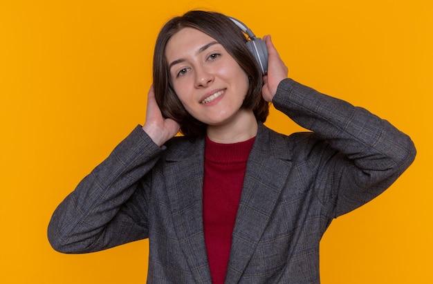Glückliche junge frau mit kurzen haaren, die graue jacke mit kopfhörern trägt, die ihre lieblingsmusik genießt, die fröhlich über orange wand stehend lächelt
