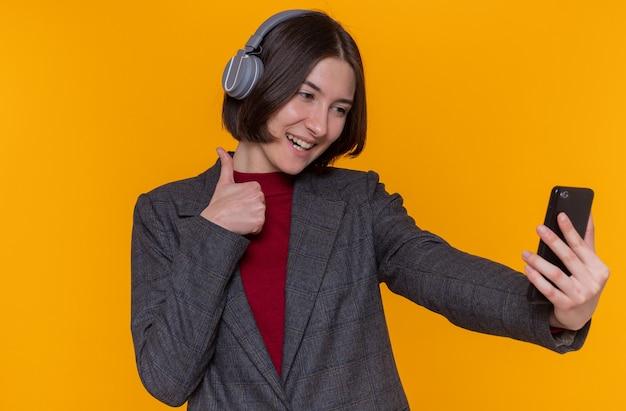Glückliche junge frau mit kurzen haaren mit kopfhörern, die graue jacke tragen, die bildschirm ihres handys betrachtet und daumen hoch zeigt, die fröhlich lächeln
