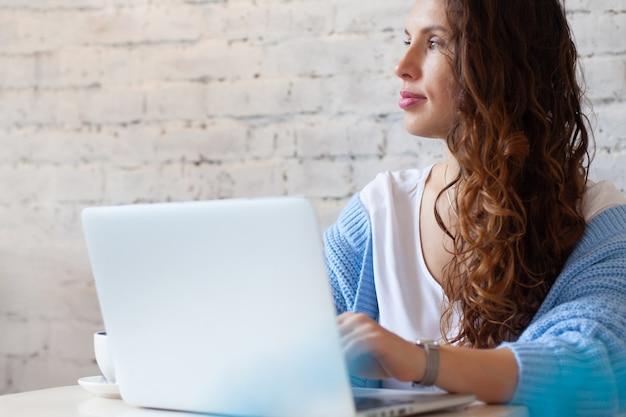 Glückliche junge frau mit langen haaren in blau gestricktem warmem pullover, der nahe am fenster sitzt und ferngesteuert zu hause am computer arbeitet. wohnraum mit fensterblick. elegante geschäftsfrau lächelt.