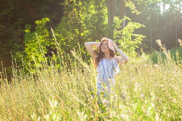 Glückliche junge frau mit langen haaren in hut und kleid zieht ihre hände in richtung der pflanzen, während sie an einem sonnigen tag durch den sommerwald geht. sommerfreude