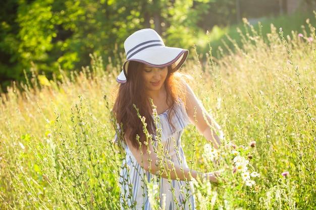 Glückliche junge frau mit langen haaren in hut und kleid zieht ihre hände zu einer pflanze während des gehens