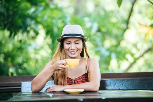 Glückliche junge frau mit lattekaffee am morgen