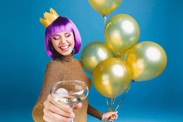 Glückliche junge frau mit lila haarschnitt, krone auf kopf feiern mit goldenen luftballons und champagner. luxuskleid, neujahrsparty, geburtstag, lächeln mit geschlossenen augen.