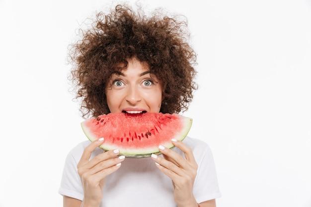 Glückliche junge frau mit lockigem haar, das wassermelone isst
