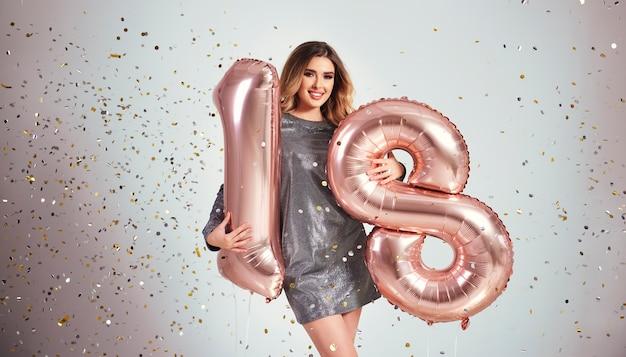 Glückliche junge frau mit luftballons, die ihren geburtstag feiern