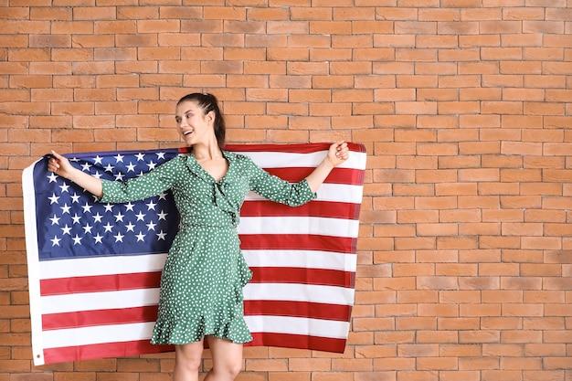 Glückliche junge frau mit nationalflagge der usa auf backsteinhintergrund