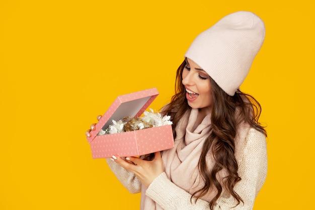 Glückliche junge frau mit offenem mund öffnet eine geschenkbox mit weihnachtsgeschenk, mädchen schaut in die geschenkbox und lacht vor glück. das konzept der geschenke und überraschungen für das neue jahr und weihnachten.