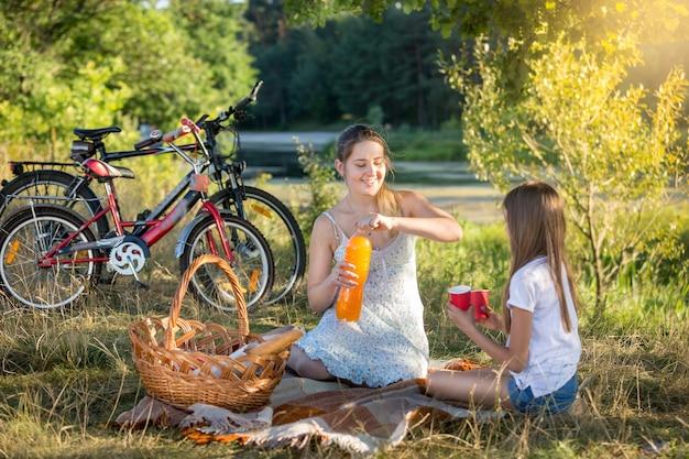 Glückliche junge frau mit picknick am fluss mit 10-jähriger tochter.