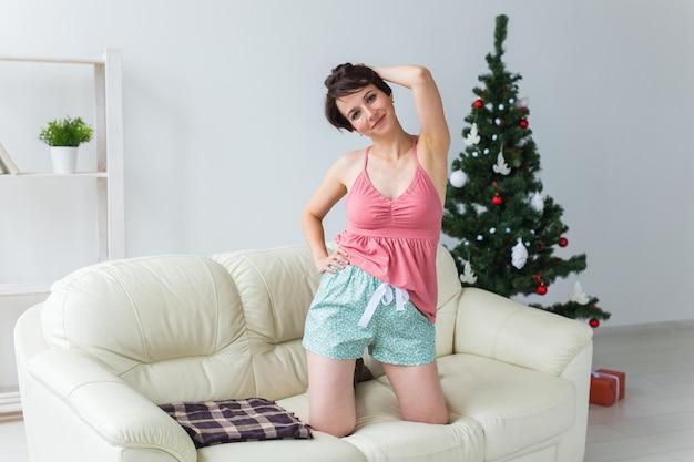 Glückliche junge frau mit reizendem hund im wohnzimmer mit weihnachtsbaum. urlaubskonzept.