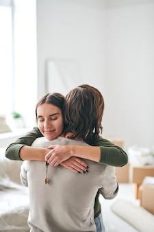 Glückliche junge frau mit schlüssel von der neuen wohnung, die ihren ehemann umarmt, während sie in einem der räume ihrer neuen wohnung oder ihres neuen hauses steht