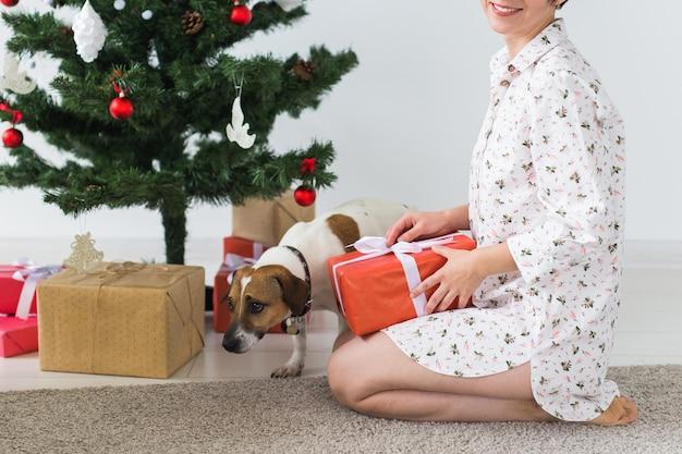 Glückliche junge frau mit schönem hund, der geschenkbox unter weihnachtsbaum öffnet. urlaub konzept.