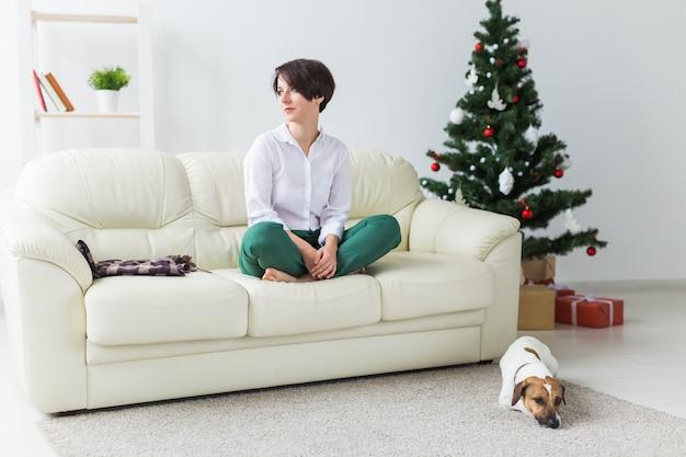 Glückliche junge frau mit schönem hund im wohnzimmer mit weihnachtsbaum. urlaub konzept.