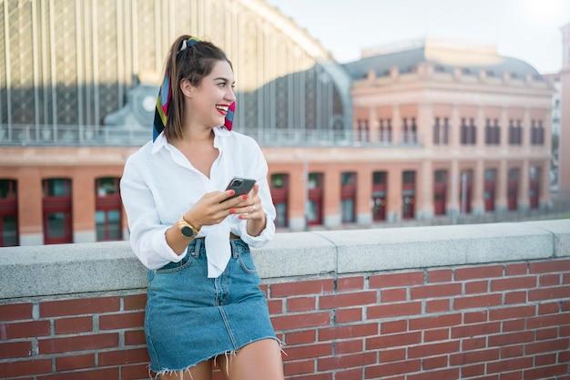 Glückliche junge frau mit smartphone. sie schaut weg. sie trägt ein weißes hemd und einen jeansrock. sie wird auf ziegelmauer gestützt. sie ist gegen das bauen.
