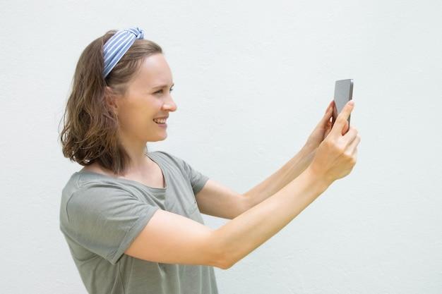 Glückliche junge frau mit tablette, die bilder macht