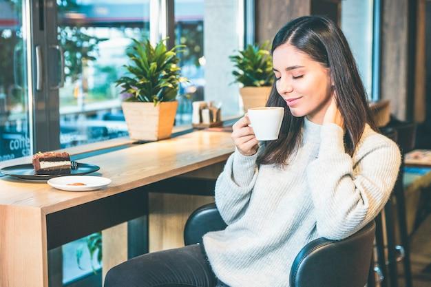 Glückliche junge frau mit tasse kaffee, die durch ein fenster im café mit geschlossenen augen sitzt