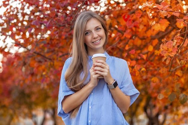 Glückliche junge frau mit tasse kaffee, zum auf autumn red trees zu gehen