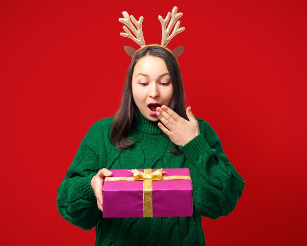 Glückliche junge frau mit weihnachtshirschgeweih mit geschenk auf rot lokalisiert