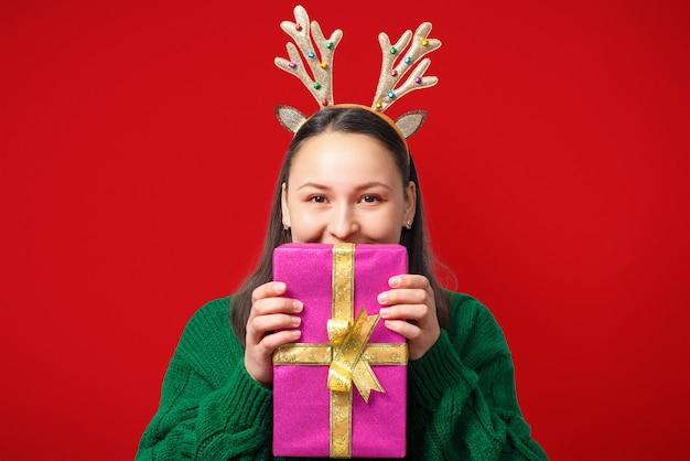 Glückliche junge frau mit weihnachtshirschgeweih mit geschenk auf rot