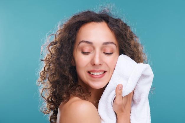 Glückliche junge frau mit zahnigem lächeln und langem, gewelltem haar, das ihr gesicht mit einem weichen weißen handtuch nach der morgendlichen hygiene auf blau berührt