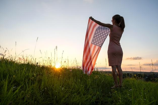 Glückliche junge frau posiert mit der nationalflagge der usa, die bei sonnenuntergang im freien steht. positive frau, die den unabhängigkeitstag der vereinigten staaten feiert. internationaler tag des demokratiekonzepts.