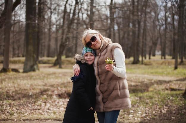 Glückliche junge frau posiert mit ihrem sohn im park
