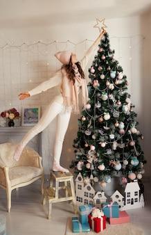 Glückliche junge frau schmückt den weihnachtsbaum. ein mädchen in einem pullover setzt einen stern auf einen weihnachtsbaum. neujahrs- und weihnachtsferienkonzept.