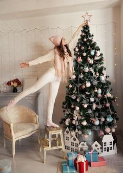 Glückliche junge frau schmückt den weihnachtsbaum. ein mädchen in einem pullover setzt einen stern auf einen weihnachtsbaum.