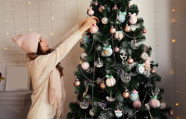 Glückliche junge frau schmückt den weihnachtsbaum hängen den ball an den baum. weihnachtsdekoration, spielzeug, das am baum hängt, weihnachtsbaumkugel.